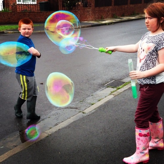 Even blowing giant bubbles is more fun in the rain!