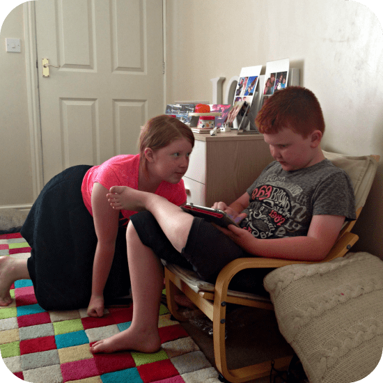 Miss F teaching her little brother how to use an app.